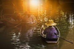 Femme naviguant le bateau marchand thaïlandais dans le les plus populaires de flottement t de maket images libres de droits