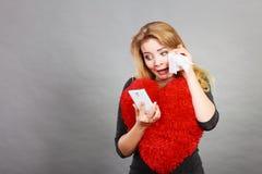 Femme navrée triste regardant son téléphone Photos libres de droits