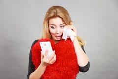 Femme navrée triste regardant son téléphone Image stock