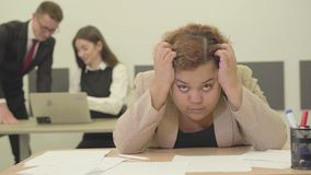 Femme nerveuse s'asseyant à la table dans le premier plan tenant sa tête avec des mains, elle a le problème au travail jeune banque de vidéos