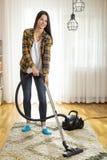Femme nettoyant ? l'aspirateur le tapis photographie stock libre de droits
