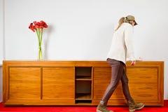 Femme nettoyant la commode en bois brune vide avec trois fleurs sur la voiture rouge carped photographie stock