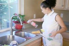 Femme nettoyant la cuisine Photographie stock