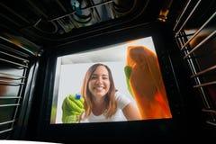 Femme nettoyant la porte en verre du four images libres de droits