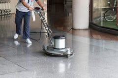 Femme nettoyant le plancher avec la machine de polissage photographie stock