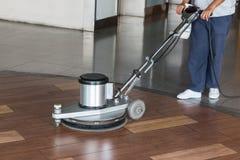 Femme nettoyant le plancher avec la machine de polissage images stock