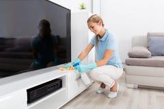 Femme nettoyant les meubles du salon Photographie stock
