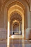 Femme non identifiée marchant sous la voûte du complexe de bâtiment du sultan, dans Muscat Photos stock