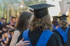 Femme non identifiée recevant un diplôme tandis qu'un ami se tient près de elle Photos stock