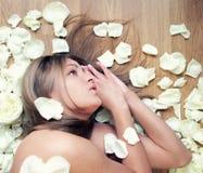 Femme nue autour extrêmement bronzée dans des pétales de rose de station thermale Photographie stock libre de droits
