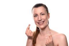 Femme nue de sourire tenant le fil dentaire Photographie stock