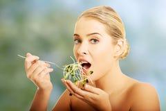 Femme nue en bonne santé mangeant le cuckooflower Image stock