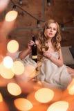 Femme nue enveloppée dans une couverture avec la bouteille et le verre de vin blanc Belle fille blonde appréciant l'alcool confor photos libres de droits