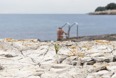 Femme nue se baignant dans la plage rocheuse de mer avec l'échelle Photographie stock libre de droits