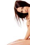 Femme nue se mettant à genoux sur le plancher