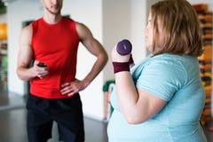 Femme obèse établissant avec des haltères photographie stock
