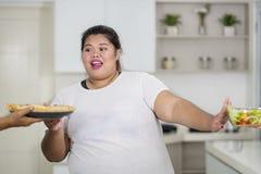 Femme obèse asiatique choisissant la pizza image libre de droits