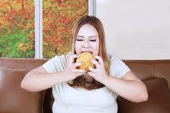 Femme obèse avide appréciant un hamburger photographie stock
