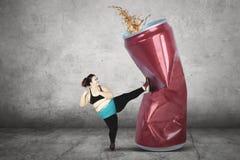 Femme obèse donnant un coup de pied la boisson non alcoolisée Photographie stock