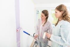 Femme observant à son ami peignant le mur photos stock