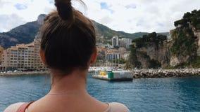 Femme observant des hôtels au littoral, logement abordable pour des touristes banque de vidéos