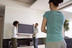 Femme observant deux hommes déplacer la télévision de plasma Photos stock