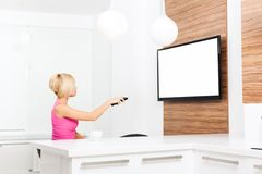 Femme observant la prise de TV à télécommande Image stock
