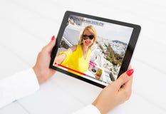 Femme observant le blogger visuel en ligne sur la tablette photographie stock libre de droits
