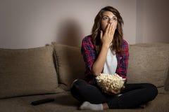 Femme observant un film d'horreur images libres de droits