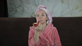 Femme observant un film de fin de nuit à la TV, mangeant une pomme Peignoir, masque facial banque de vidéos