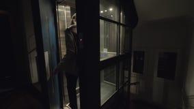 Femme obtenant en haut utilisant l'ascenseur banque de vidéos