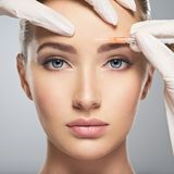 Femme obtenant l'injection cosmétique de botox dans le front image stock