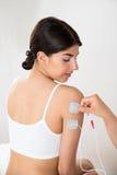 Femme obtenant la thérapie d'électrodes en main Images libres de droits