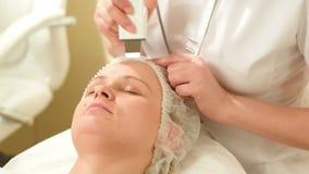 Femme obtenant le nettoyage ultrasonique de visage à la beauté clips vidéos