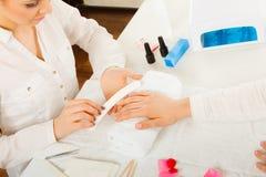 Femme obtenant les ongles de dossier faits par manucure Image stock