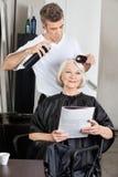 Femme obtenant lui des cheveux faits dans le salon Images stock