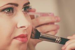 Femme obtenant lui le maquillage fait avec la brosse professionnelle Image stock