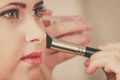 Femme obtenant lui le maquillage fait avec la brosse professionnelle Photos stock