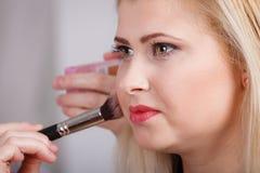 Femme obtenant lui le maquillage fait avec la brosse professionnelle Images libres de droits