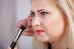 Femme obtenant lui le maquillage fait avec la brosse professionnelle Image libre de droits