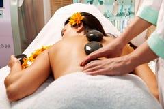 Femme obtenant un massage en pierre chaud dans le salon de station thermale photographie stock