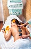 Femme obtenant un massage en pierre chaud dans le salon de station thermale photographie stock libre de droits