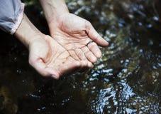 Femme obtenant une certaine eau de la rivière pour boire Photos libres de droits