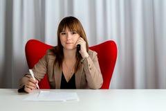 Femme occasionnelle à l'écriture de bureau avec le stylo et à parler par le téléphone Photographie stock