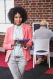 Femme occasionnelle à l'aide du comprimé numérique avec le collègue derrière dans le bureau image libre de droits