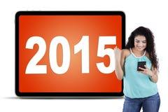 Femme occasionnelle avec le téléphone portable et les numéros 2015 Photographie stock libre de droits