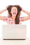 Femme occasionnelle choquée avec des verres regardant l'ordinateur portable et le plumant Photo stock