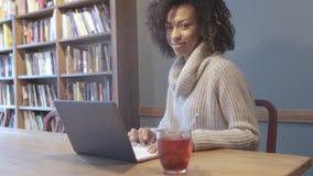 Femme occasionnelle d'étudiant s'asseyant au café et à l'aide de l'ordinateur portable banque de vidéos
