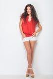 Femme occasionnelle de sourire se tenant avec ses jambes croisées Image stock