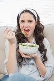 Femme occasionnelle magnifique sur le divan confortable mangeant de la salade Images libres de droits